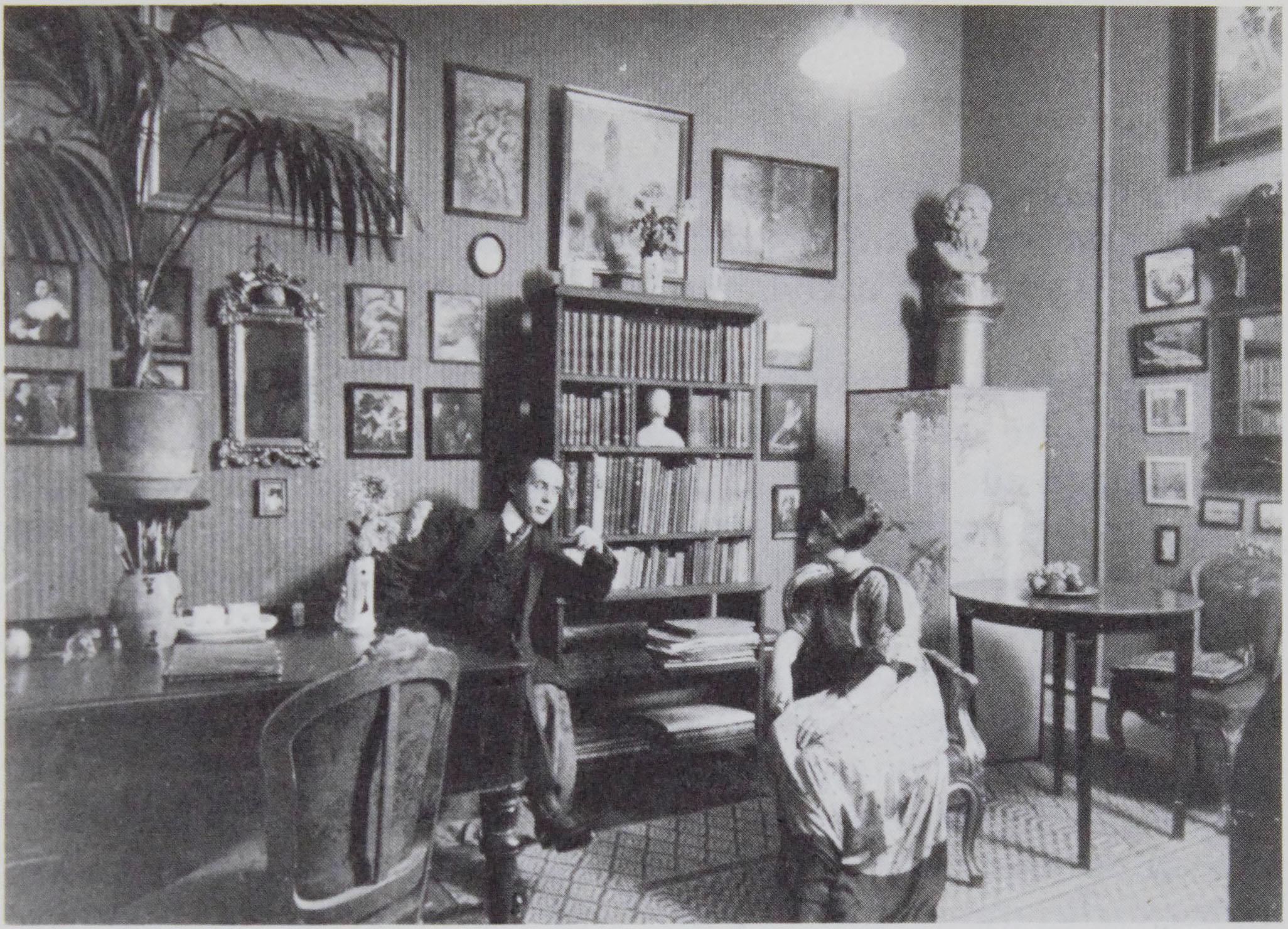 The photo is at the top of the page and is credited to                      Politiken Press. It shows Einar and Gerda Wegener sitting in chairs a few feet                      apart in a room in their home that is filled with art and books.