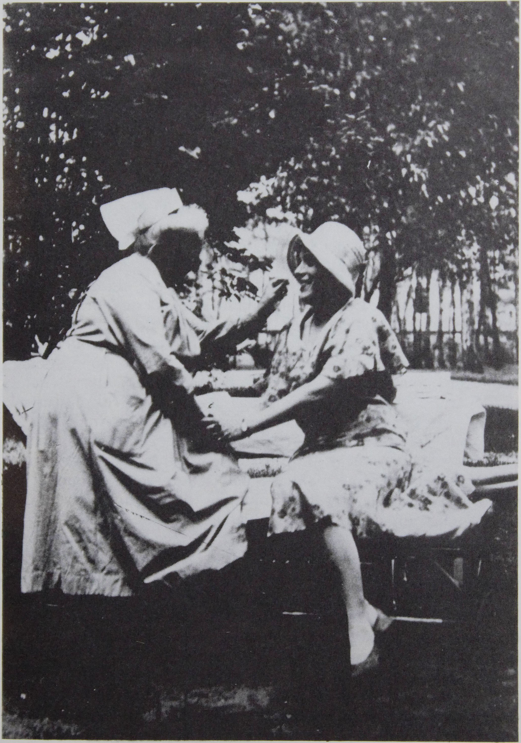 The photo, which takes up the whole page along with the                      caption, is credited to The Royal Library, The Collection of Prints and                      Photographs. It shows Lili Elbe dressed in dress, pumps, and hat outside the                      Frauenklinik in Dresden with a nurse after surgery.