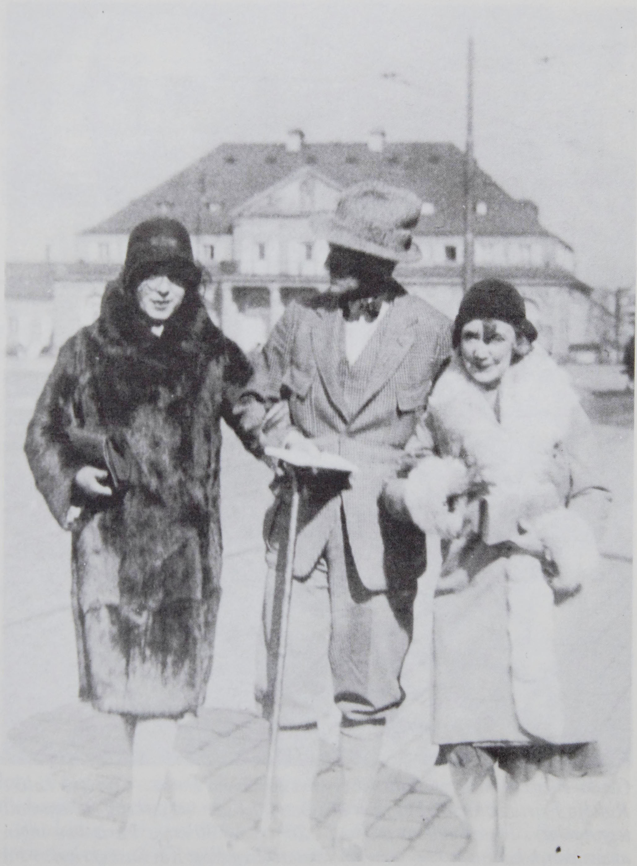 The photo, which takes up the whole page along with the                      caption, is credited to The Royal Library, The Collection of Prints and                      Photographs. It captures Lili Elbe, Poul Knudsen and Gerda Wegener outside,                      most likely in Berlin, dressed in coats and hats.