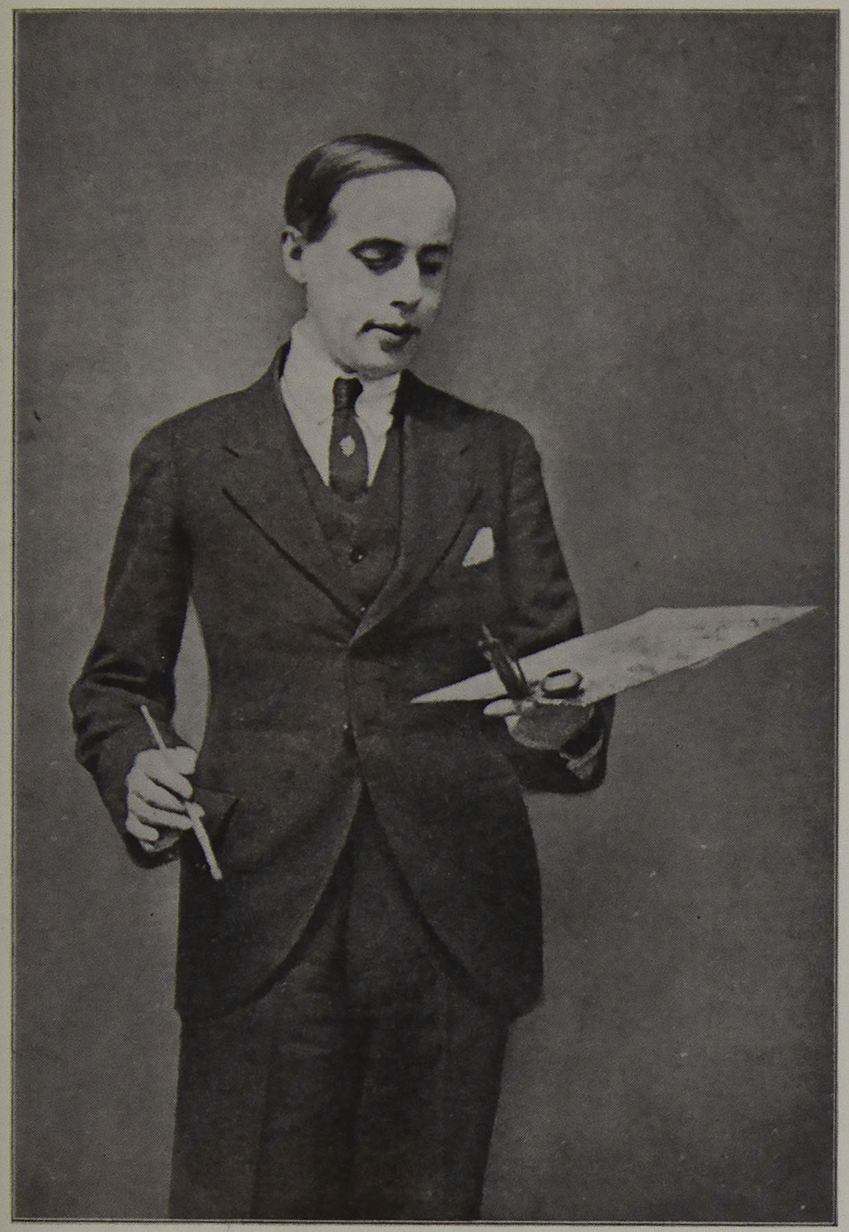 Einar Wegener is dressed in                      a suit and holds painting materials.