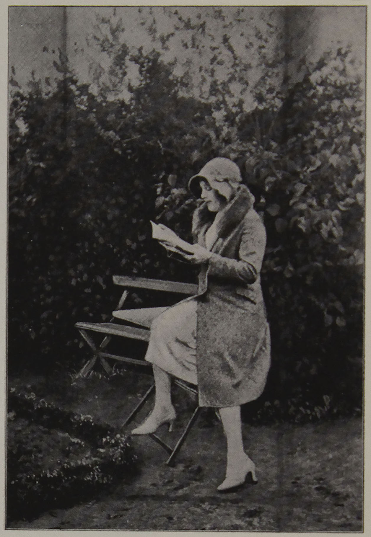 Lili Elbe is outside, sitting                      on a chair or bench and reading a book.