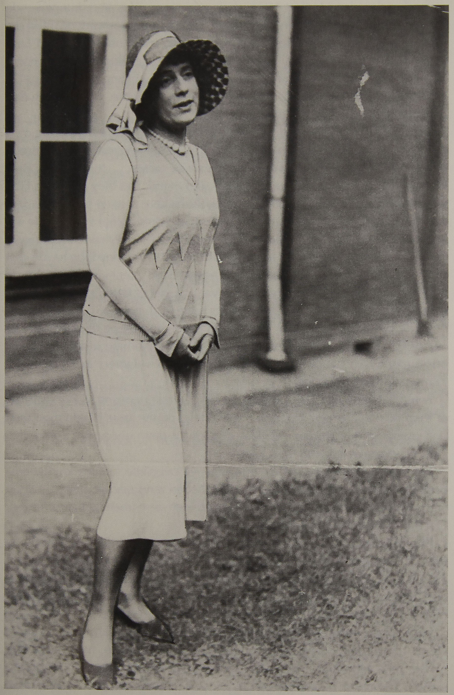Lili Elbe stands outside with                      hands clasped in front and is dressed in a skir, shirt, hat, and dress                      shoes.